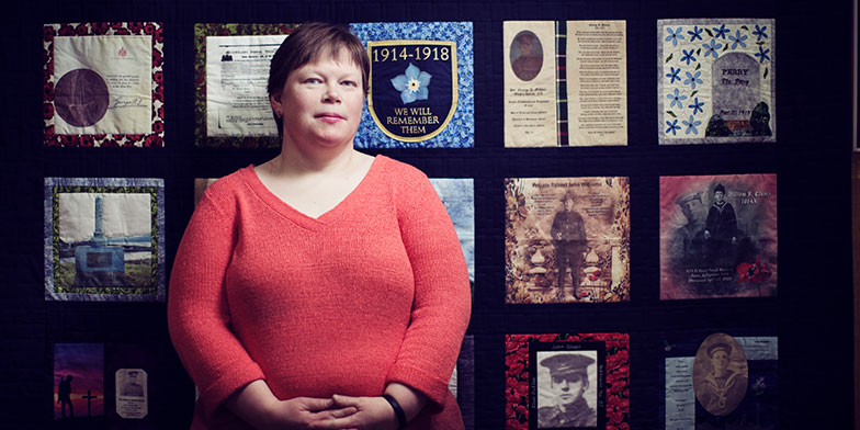 Tracy Madore in front of Peace-by-Piece: Quilted Memories of Newfoundland in the Great War