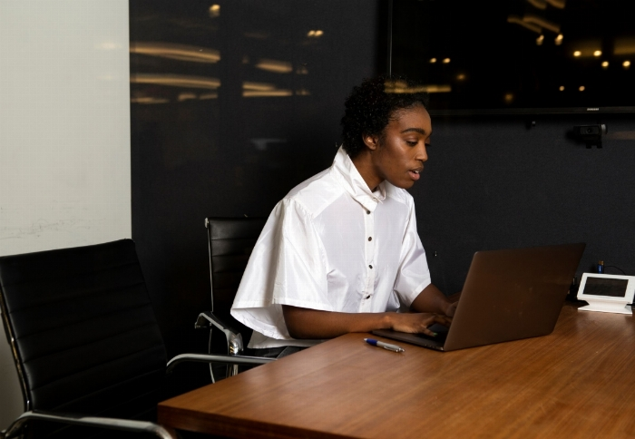 A non-binary person using a laptop