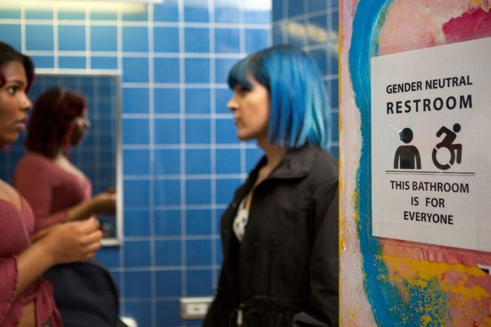 two people talking in a gender neutral washroom